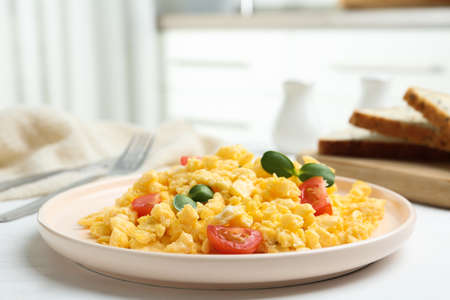 Tasty scrambled eggs with sprouts and cherry tomato on white wooden table