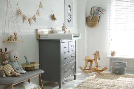 Beautiful baby room interior with toys and modern changing table