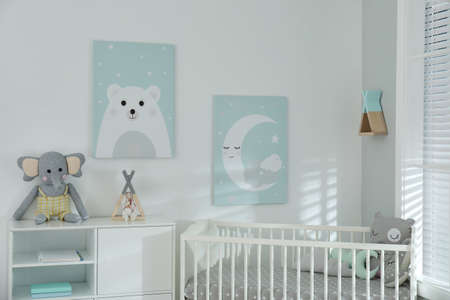 Stylish baby room interior with crib and cute pictures on wall Standard-Bild