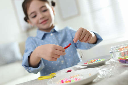 Little girl making accessory with beads at table indoors, focus on hands. Creative hobby Stock Photo