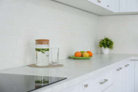 Drink, fruits and houseplant on counter in kitchen. Interior design