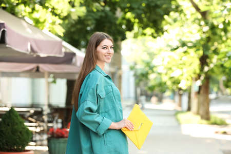 Beautiful young woman with elegant envelope bag outdoors on summer day