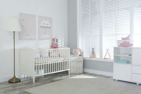Stylish baby room interior with crib and cute pictures on wall