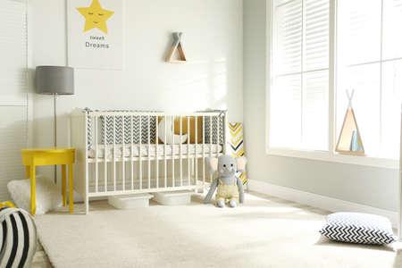 Cute baby room interior with crib and big window