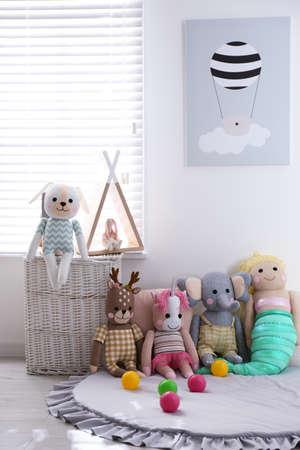 Funny stuffed toys on floor near window. Decor for children's room interior