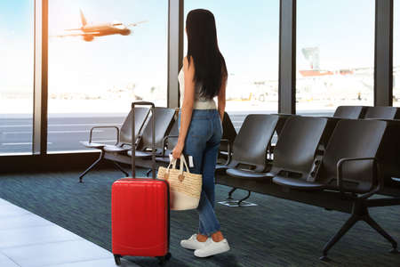Woman with bag and travel suitcase at airport terminal. Summer vacation Standard-Bild