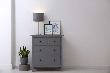 Gray chest of drawers in stylish room interior. Space for text