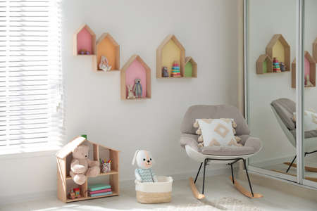 Cute children's room with house shaped shelves and rocking chair. Interior design