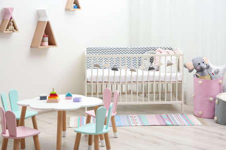 Cute baby room interior with cot and little table Stockfoto