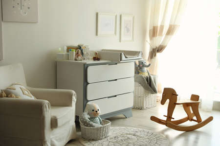 Beautiful baby room interior with toys, armchair and modern changing table Standard-Bild