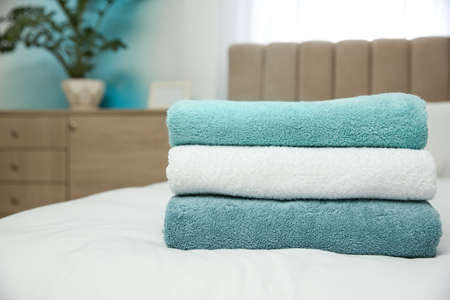 Soft clean towels on bed at home