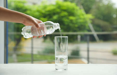 Woman pouring water from bottle into glass on table against blurred background, closeup
