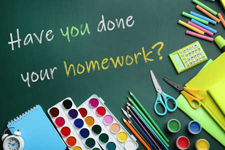 School stationery and phrase HAVE YOU DONE YOUR HOMEWORK? on chalkboard, flat lay