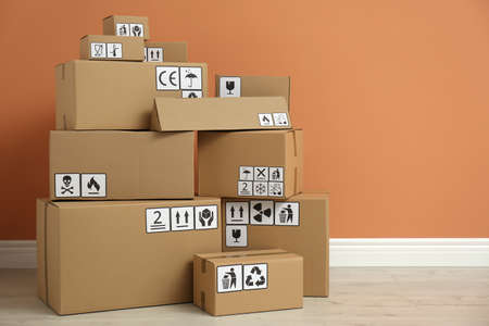 Cardboard boxes with different packaging symbols on floor near orange wall. Parcel delivery