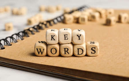 Beads with word KEYWORDS on notebook, closeup