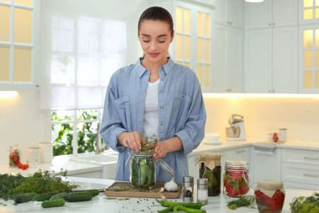 Woman putting dill into pickling jar at table in kitchen