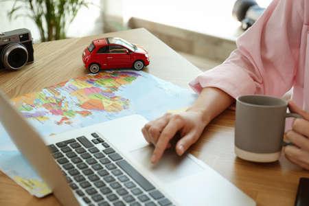 Woman using laptop to plan trip at wooden table, closeup