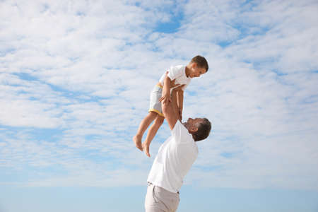 Grandfather playing with cute little boy outdoors Standard-Bild