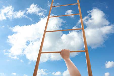 Woman climbing up wooden ladder against blue sky with clouds, closeup Foto de archivo