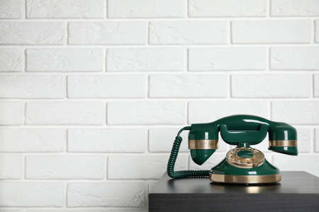 Green vintage corded phone on small black table near white brick wall. Space for text Banco de Imagens