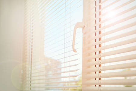 Beautiful view through window with blinds on sunny day, closeup