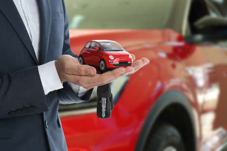 Car buying. Man holding key and model against blurred automobile, closeup