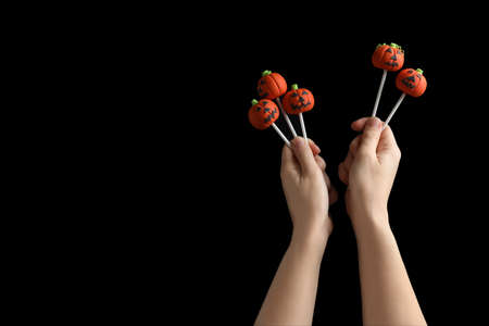 Woman with delicious pumpkin shaped cake pops and space for text on black background, closeup. Halloween celebration