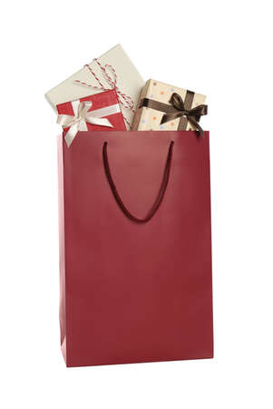 Paper shopping bag full of gift boxes isolated on white