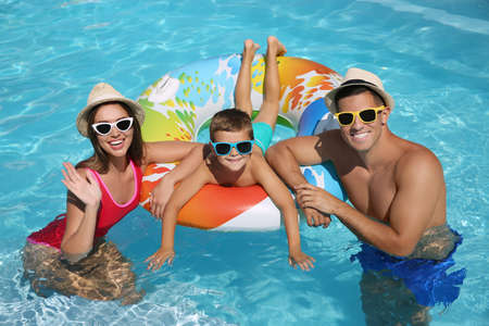 Happy family with inflatable ring in swimming pool Stockfoto