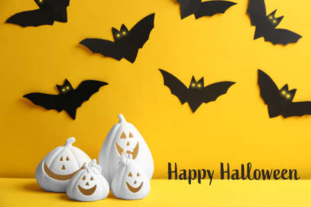 Happy Halloween greeting card design. Jack-o-Lantern candle holders and paper bats on yellow background