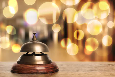 Wooden table with hotel service bell on blurred background. Space for text