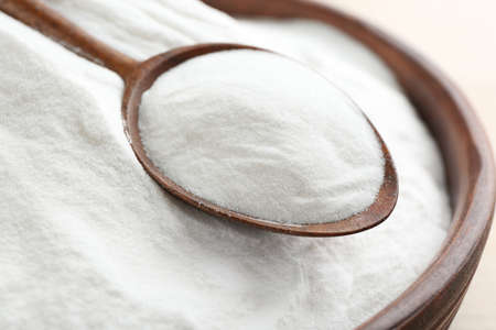 Bowl and spoon with baking soda, closeup Stock Photo
