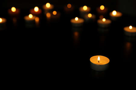 Many burning tealight candles on dark background, space for text