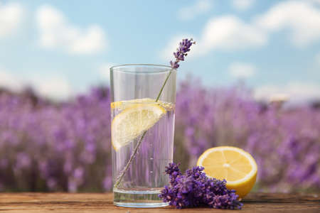 Lemonade with lemon slices and lavender flowers on wooden table outdoors, closeup Banque d'images