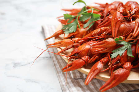 Delicious boiled crayfishes on white marble table, closeup. Space for text Stockfoto