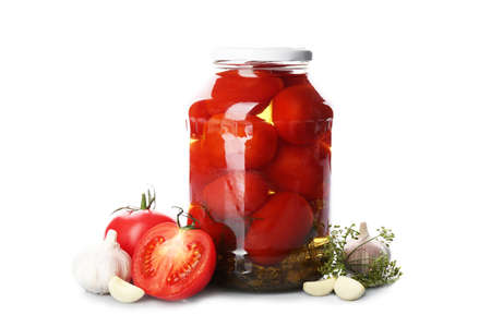 Jar of pickled tomatoes and fresh ingredients on white background