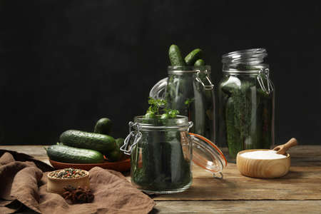 Pickling jars with fresh ripe cucumbers and spices on wooden table
