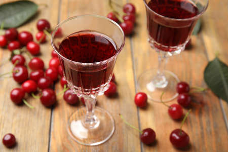 Delicious cherry wine with ripe juicy berries on wooden table