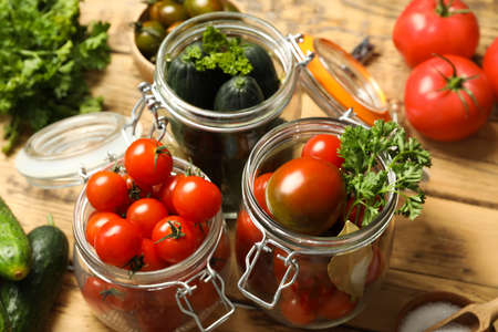 Pickling jars with fresh ripe vegetables and spices on wooden table, closeup