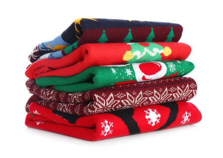 Stack of warm Christmas sweaters isolated on white