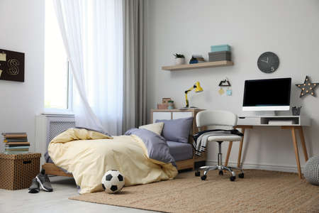Stylish teenager's room interior with comfortable bed and workplace