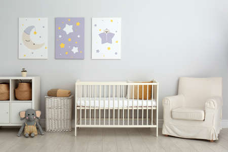 Baby room interior with crib and cute posters on wall