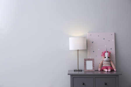 Modern gray chest of drawers near light wall in child room, space for text. Interior design