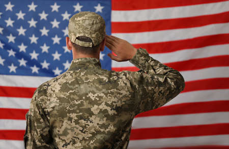 Male soldier in uniform against USA flag, back view
