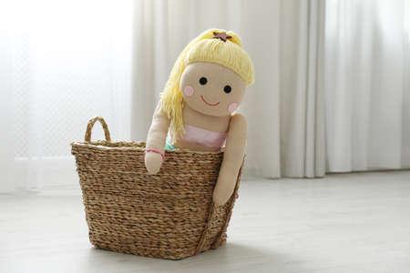 Funny doll in basket on floor. Decor for children's room interior