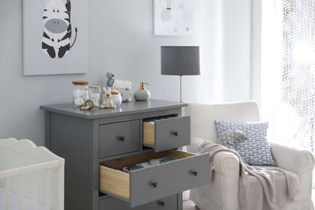 Modern open chest of drawers with baby clothes and accessories in room