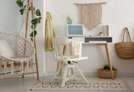 Stylish room interior with workplace and hanging chair