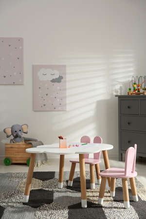 Little table and chairs with bunny ears in children's room. Interior design