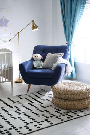 Cozy baby room interior with comfortable armchair