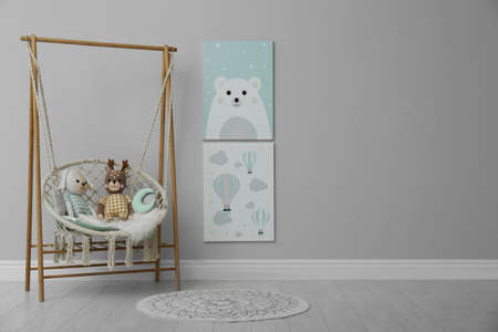 Stylish child's room interior with adorable paintings and hanging chair. Space for text